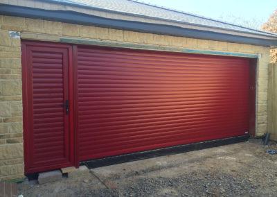 Burgundy red roller door with matching pass door