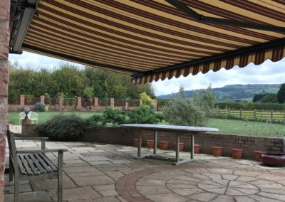 Red striped fabric ascot awning with DB703 cassette